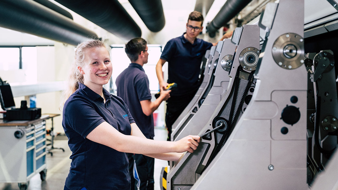 young female trainee stands smiling in front of a machine